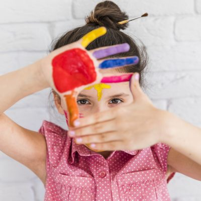 portrait-girl-looking-through-her-painted-hands-standing-against-white-brick-wall
